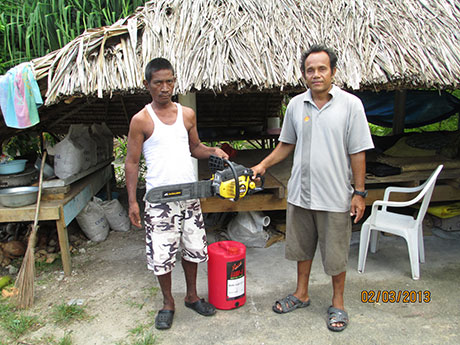 Wayne presents Taunteang, a former leprosy patient, with a chainsaw, fuel can and fuel to enable Taunteang to earn a living. Employment opportunities are scarce in Kiribati, but with most structures built of wood, Taunteang can now work as a builder.
