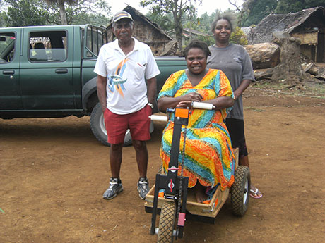 When Isaac got his disability scooter, it was his idea for his old wheelchair to be given to another patient. Here, Vearu receives her new wheelchair which will give her much more independence. She struggles to walk as she suffers from drop foot as a result of leprosy. Behind her are the driver and Isaac's wife, Verongi.